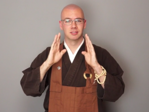 Image: Image from footage of a video of Ōshin R. Liam Jennings, deaf Zen Buddhist monk, wearing rakusu and samue. He is signing 'ATTENTIVE' in ASL.